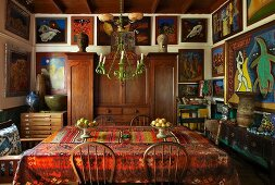 Dining room with closely spaced gallery of pictures on walls