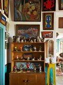 Small sporting figurines displayed on dresser shelves below gallery of artworks