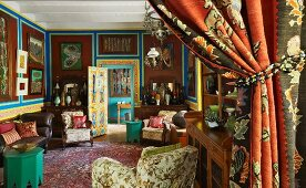 Profusion of patterns and paintings on walls painted earthy brown in large interior