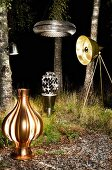 Various lit lamps arranged in front of birch trunks in dark woods at night
