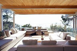 Sofa combination in terrace-style living room; smooth wooden ceiling supported on steel girders