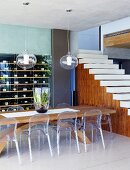 Plexiglass chairs at massive wooden table; wine rack and open-plan staircase without bannister in background