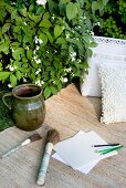 Painting utensils and paper next to jug on rug in garden