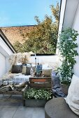Simple table made from fruit crates next to inviting sofa with fur blanket in narrow roof recess open to sky
