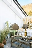Fruit crates and wire mesh upcycled into rustic coffee table and wildlife decor such as musk ox horn and animal-skin blanket in seating area on roof terrace