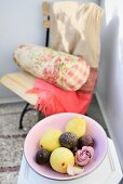 Fruit and rose in dish; garden chair with Oriental blanket and floral bolster in blurry background