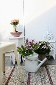Bouquet of phlox in watering can on sequinned rug, white Marrakesh lamp and side table in background create Oriental atmosphere on roof terrace