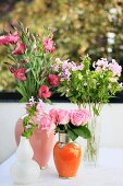 Bouquets of lisianthus and roses in Moroccan ceramic vases with metal ornamentation, pale purple phlox in glass vases