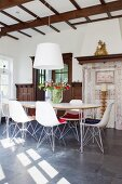 Classic chairs in front of traditional tiled stove with hand-made tiles in dining area