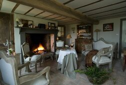Cosy room with fireplace, low beamed ceiling and brick floor; vintage seating in front of open fire