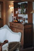 Wooden dining room dresser with simple top unit; antique sofa in natural shades in foreground