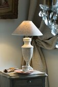 Table lamp with marble base on grey, vintage bedside table; heavy, gathered curtain in background