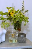 Posy in wine glass behind perfume bottle and crystal jar with metal lid