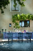 Long, set dining table with patterned tablecloth and blue wooden chairs outside restored property in southern France