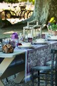 Wooden table set in shades of purple in garden