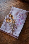 Silver spoons with twisted stems on embroidered linen napkin on old wooden table
