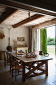 Large wooden table and rush bottom chairs under wooden ceiling of restored country house in southern France