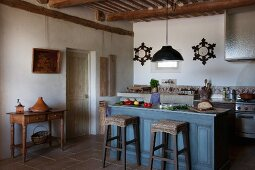 Stools with wicker seats at blue-stained island counter and console table in Provençal kitchen