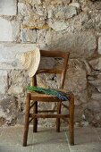 Straw hat and bouquet of lavender on Mediterranean, rush bottom chair against stone wall