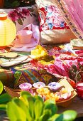 Colourful blankets, flip-flops, teacup and cushions on garden bench with flower-shaped floating candles in foreground