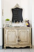 Collection of glass carafes and chalkboard on antique, shabby-chic cabinet in niche