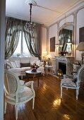 Elegant room with fireplace, large mirror on chimney breast, Baroque furniture in natural shades and glossy parquet floor