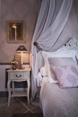 Grand bed with grey and white bed linen and scatter cushions colour-coordinated with wallpaper