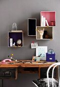 Various boxes with painted inner surfaces used as creative storage space in office