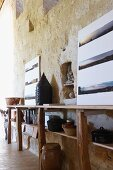 Rustic sideboard with kitchenware and sequence of panoramic photographs against sandstone wall (Chateau Maignaut)