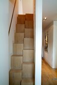 Space-saving staircase in narrow stairwell and view into modern hallway