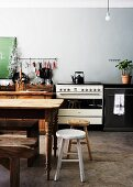 Rustic kitchen table and stools in front of improvised kitchen counter in spartan kitchen
