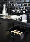 Detail of black kitchen counter with vintage-look sink and open cutlery drawer in base unit