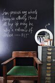 Wooden chair with green seat cushion and vintage-style, metal office cabinet in front of black chalkboard