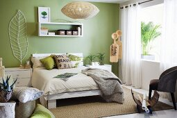 Bright, modern bedroom with pastel green wall, white furniture and sisal rug