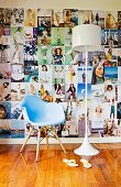 Pastel blue designer chair and white retro lamp in front of a large wall collage