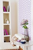 Room corner in violet, purple and white with high bookshelf and patterned wall wallpaper
