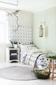 Cushions and blankets on comfortable bed with upholstered headboard panel; festive Advent arrangement of organic, natural items