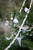 White Christmas decorations and popcorn garland on fir tree outside