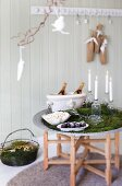 Nordic Advent arrangement with champagne, confectionery, popcorn and lit candles in bottles on tray table draped with moss