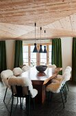 Lambskins on chairs around rustic wooden table and green curtains at windows of dining room with wooden ceiling