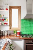 Kitchen window between green tiled wall and kitchen shelves holding various crockery and glasses