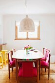 Dining table and wooden chairs with pink upholstery on stripped wooden floorboards in front of window in white wall