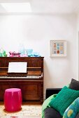 Collection of glass vessels on piano with pink barrel-shaped stool in corner of living room against white wall; black sofa in foreground