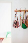 Various handbags hanging on coat rack on white wall next to open doorway