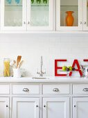 Elegant, white, country-house-style fitted kitchen with wall units; large red letters leaning on wall