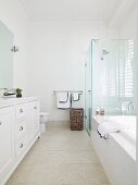 High-ceilinged bathroom in elegant, white, country-house style with glass shower partition and stone-coloured tiled floor