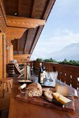 Simple lunch on wooden table on chalet balcony with view of mountain landscape