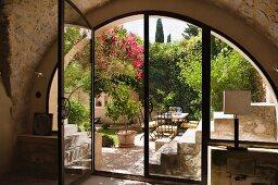 View into sunny Mediterranean courtyard through semi-circular glass wall