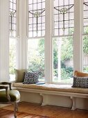 Wooden bench with pad in front of tall bay windows with traditional, lead glazed windows