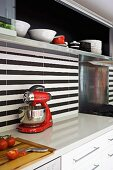 Detail of modern kitchen counter with black and white striped rear wall and wall units